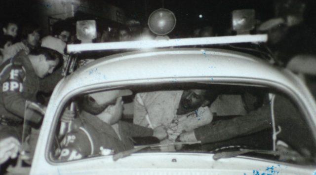 A emblemática imagem feita por Ronaldo Bernardi, fotógrafo de ZH, na década de 1980 mostra Júlio César sendo colocado com vida no carro da polícia. (Foto: Ronaldo Bernardi/divulgação)